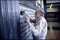 Photo of Charles Bukowski checking the PO box, 1990
